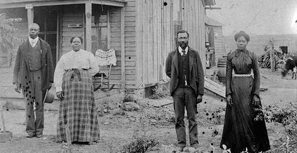 Two Black men and two black women stand in front of a frame building. Photo is black and white.