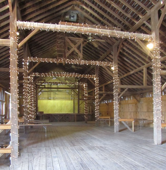Open wooden rafters, walls, and floors decorated with small, white lights.