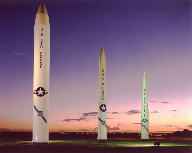 Three large missile models at sunset
