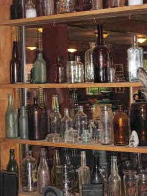 Several shelves of old bottles of various colors.