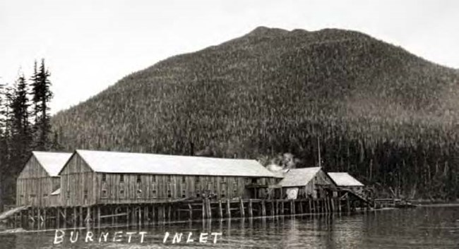 Black and white photo of long wood buildings on piers in front of trees