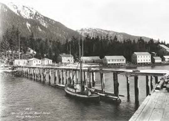 Black and white photo of a pier with buildings along the shore and mountains behind