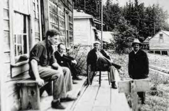 Black and white photo of four men gathered on a rough wood porch.