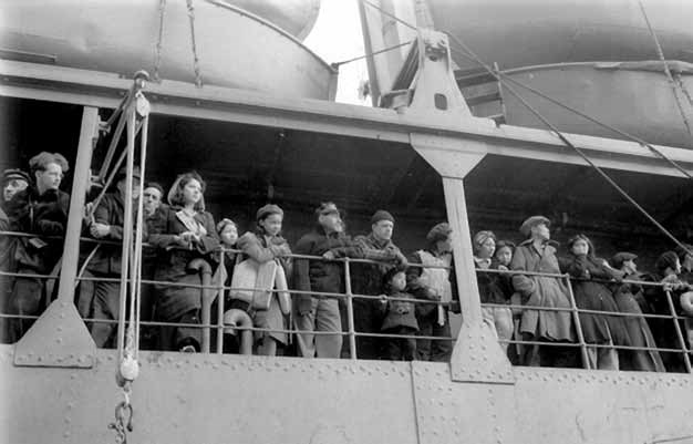Black and white photo of people at a ship railing