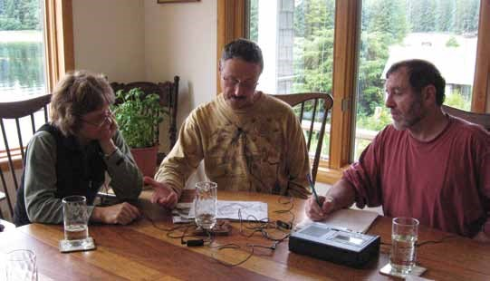 Three people sit at a table with audio recording equipment.