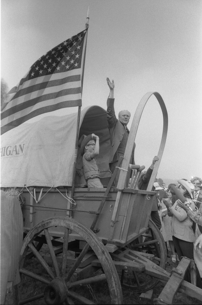 A man in a modern suit stands in a covered wagon and waves his hand.