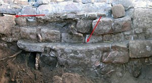 The south wall of the spring enclosure after excavation. The left arrow points to the outlet in the improved spring enclosure, the right arrow to the top of the old spring enclosure. Photograph courtesy of Emily J. Brown.