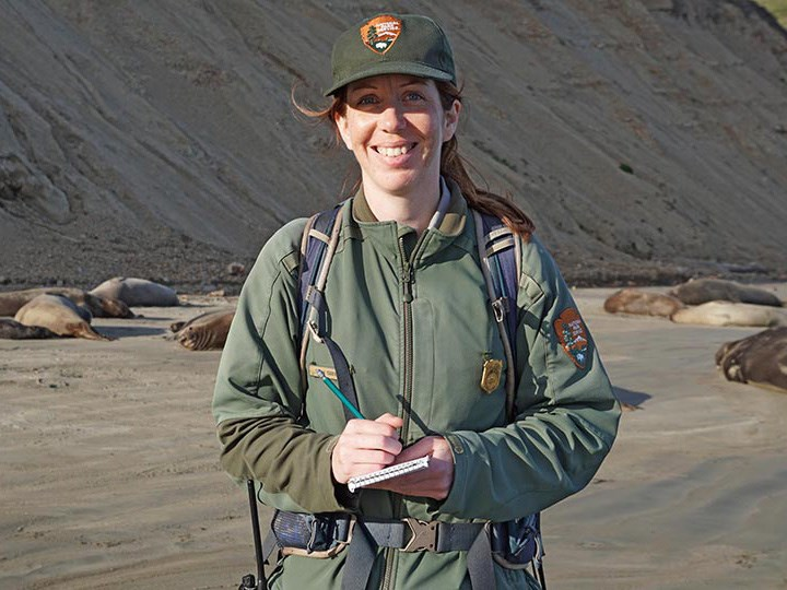 Portrait of Marine Ecologist Sarah Codde, smiling while surveying elephant seals on Drake's beach in Point Reyes.