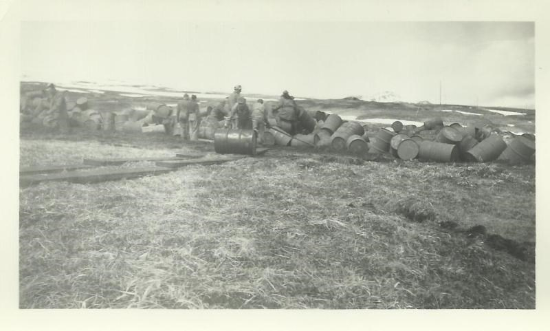 Black and white photo of men rolling barrels up an incline