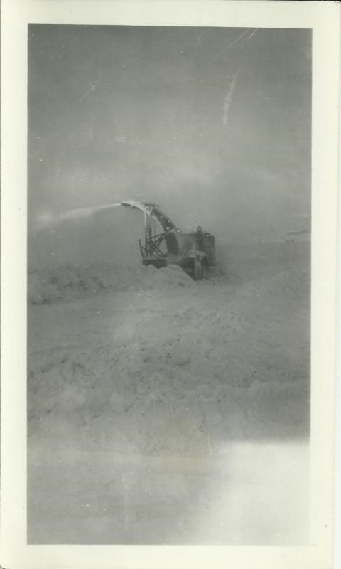 Black and white photo of a large snow plow in a snow bank