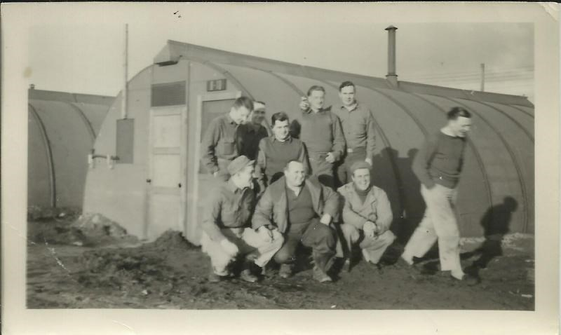 Black and white photo of men posing in front of a quonset hut