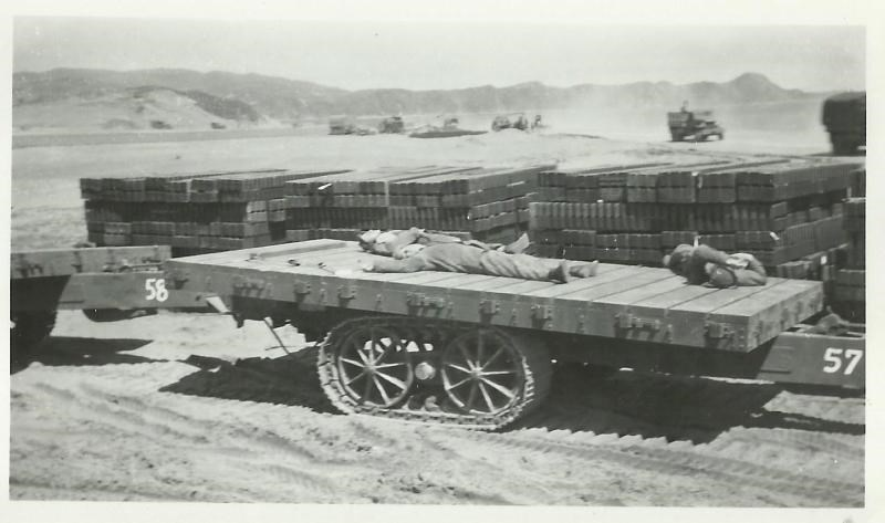 Black and white photo of men laying of a flatbed vehicle with equipment stacked behind them