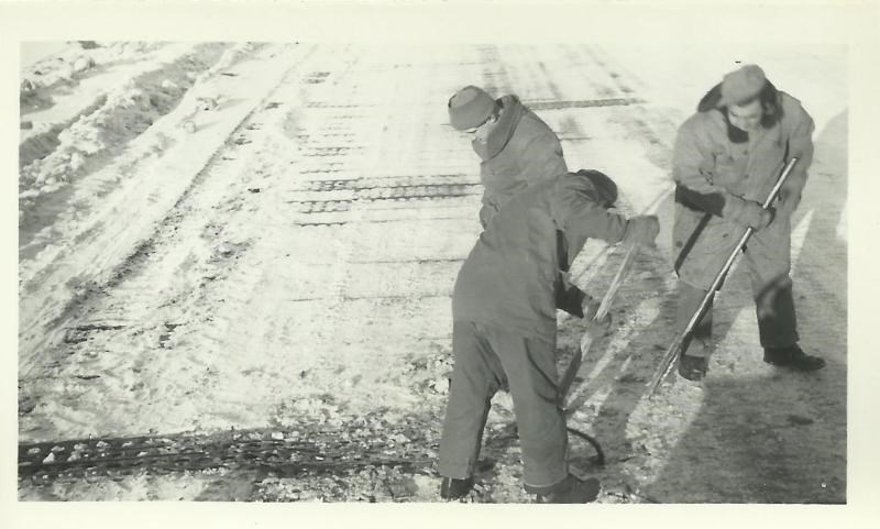 Black and white photo of men laying metal mat on snowy area
