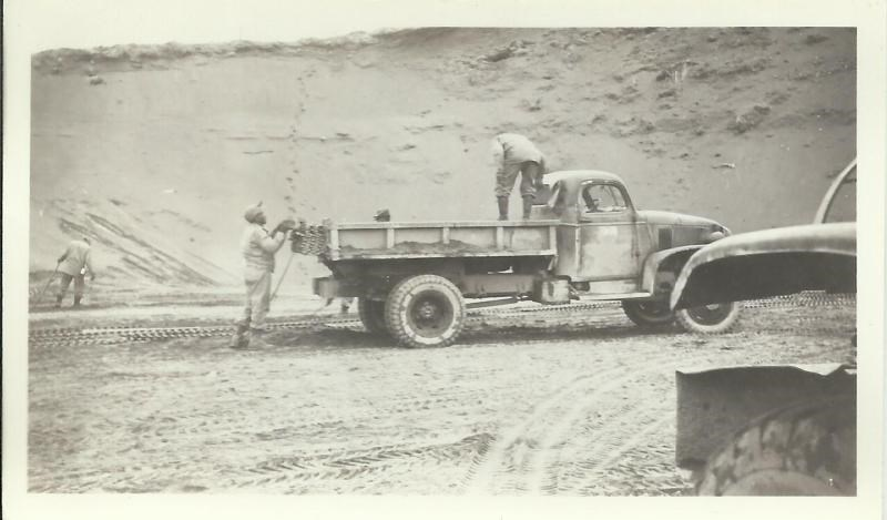 Black and white photo of men unloading wire mats from a truck with an earth bank behind them.