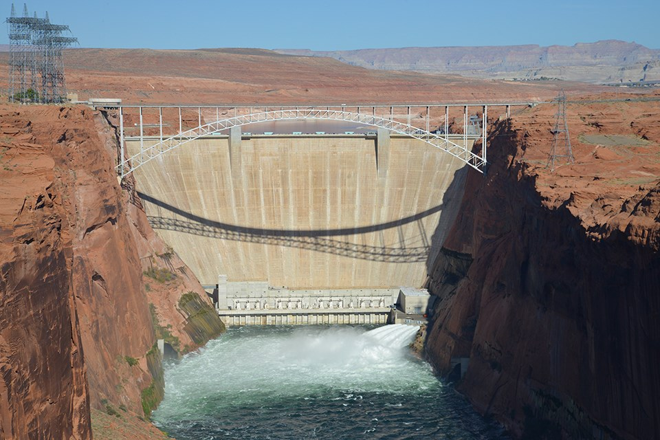 A dam with water form a river at its base and red rocky cliffs on the right and left of the dam. A bridge spans the river at the top of the cliffs. Power lines are seen at the top of the cliff on the left.