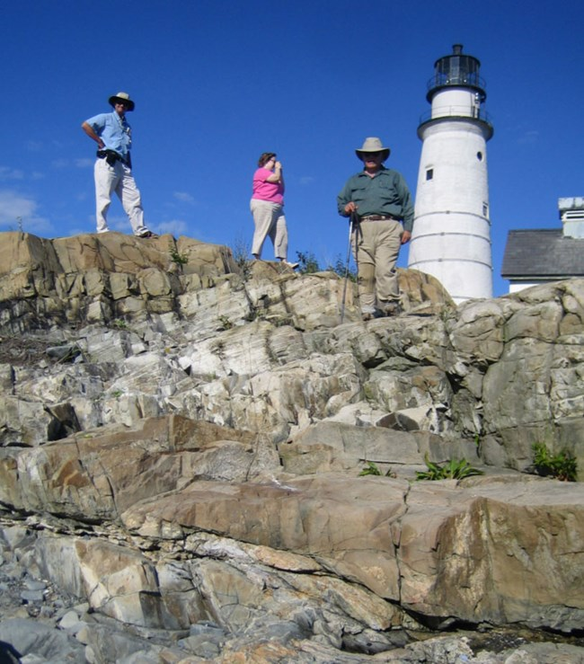 visitors and lighthouse on rocky bluff
