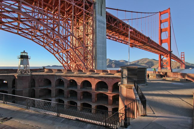 fort with golden gate bridge above