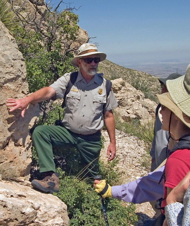 park geologist shows visitors fossils in limestone