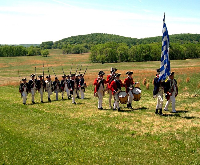 reenactment soldiers marching through meadow