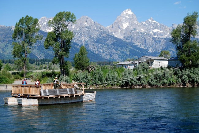 Park visitors ride a replica of Menor's Ferry along the Snake River in Grand Teton NP