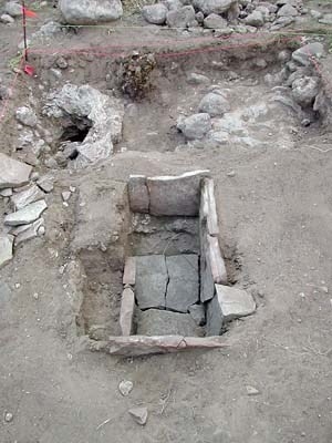 This slab-lined fire box, used for baking food, contained ashy soil and a baking powder can lid. NPS photo.
