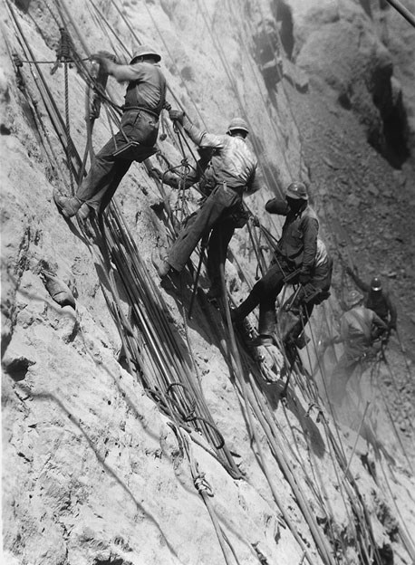 Men rappelling down side of the Hoover Dam.