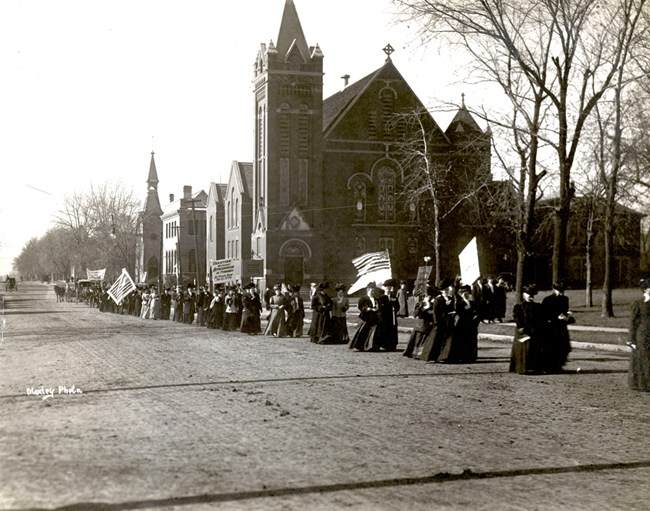 Woman suffrage procession passing by church. Women carrying flags and banners