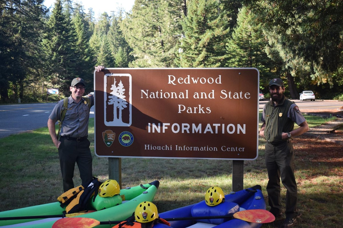 two park rangers standing by the Redwoods National and State Parks sign with two kayaks in front.