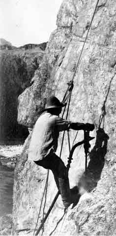 Man in a rope harness suspended against a cliff face.
