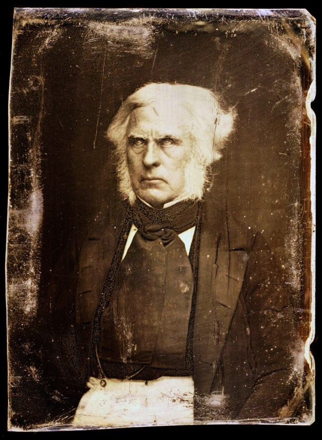 Photo portrait of man with white hair and stern expression wearing dark clothing