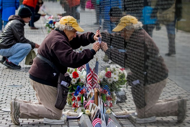 A woman in volunteer uniform kneels near a bouquet of flowers at the Vietnam Wall to get a rubbing of a name from the wall.