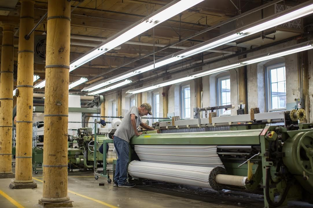 man working at loom at woolen mill