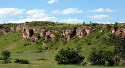 A cliff at Wind Cave National Park covered in green grass atop, red-brown jagged rocks