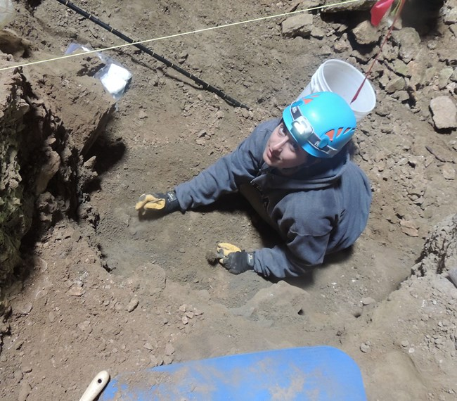 scientist digging at fossil site