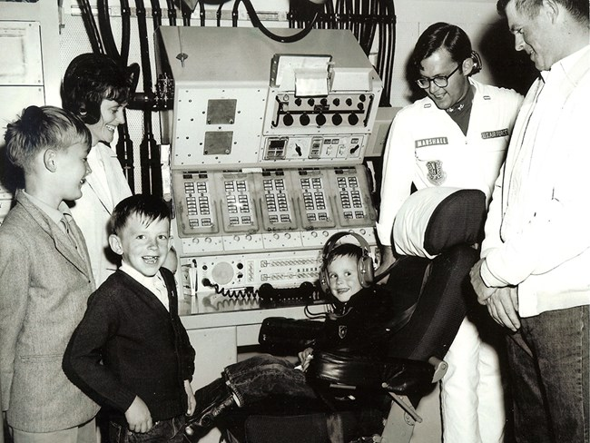 A family poses in front of a missile combat console in an underground control center