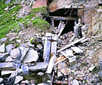 An abandoned mine cut in the side of a mountain with discarded timber and steel.