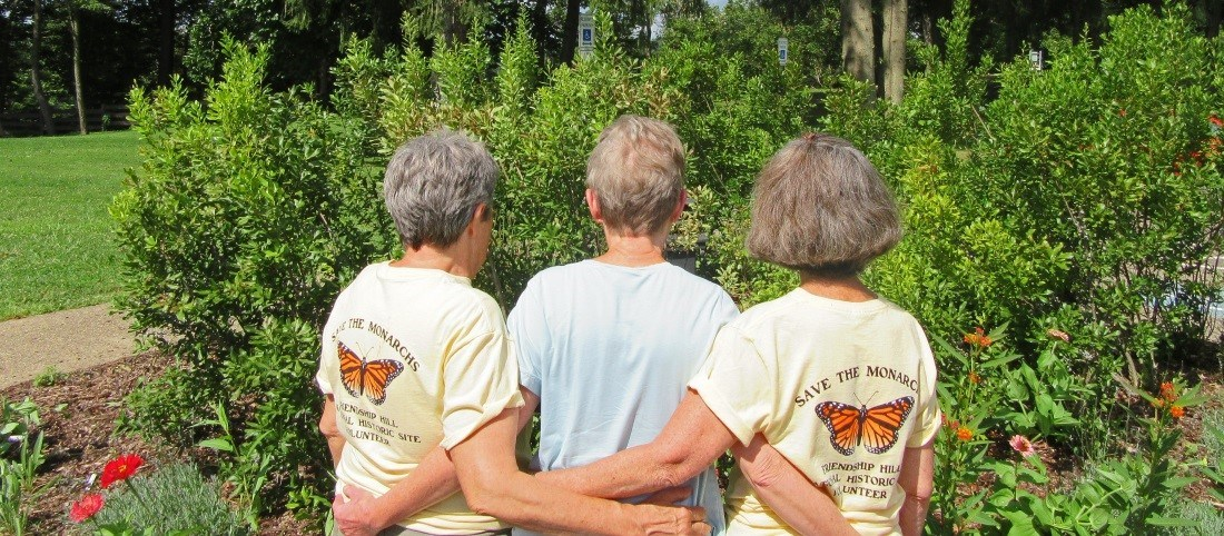 "Three ladies wearing shirts that say ""Save the Monarchs!"" stand with their backs facing the camera"