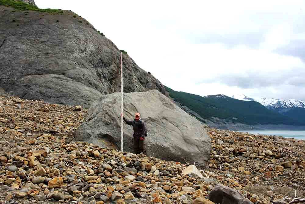 A large boulder with a man standing by it for scale.