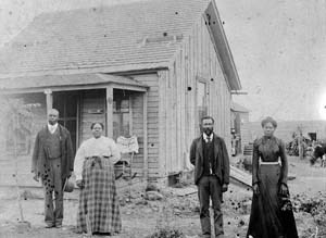 Nicodemus homesteaders pose in front of farmhouse