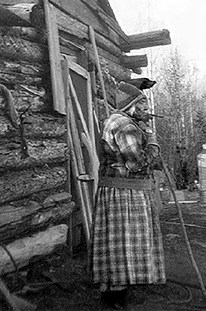 102 old women out side of log cabin 1929