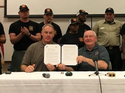 Secretary of Agriculture Sonny Perdue and Secretary of the Interior Ryan Zinke hold up their joint memo on interagency collaboration and cooperation after signing in May 2017 at the National Interagency Fire Center in Boise, Idaho. Photo courtesy of USDA.
