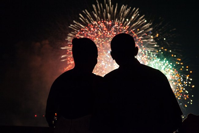 Silhouette of President and first lady Obama looking at fireworks.