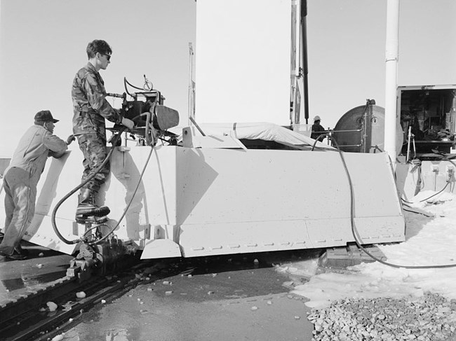 Airman works a control on the rear of a blast door