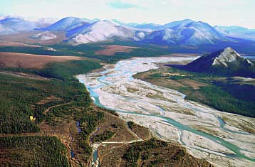 The Agashashok River runs through the mountainous region of Noatak National Preserve on a sunny day.