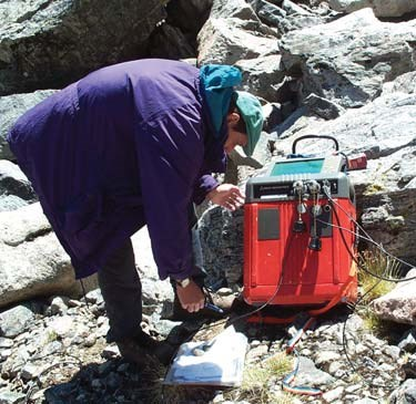 Geologist uses a large square radar device on along the ground to determine permafrost thickness.