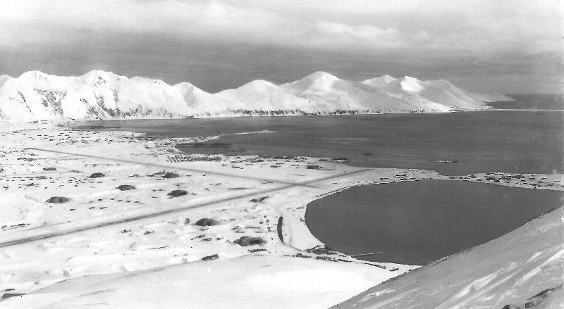 Black and white photo of snowy area and mountains along a bay