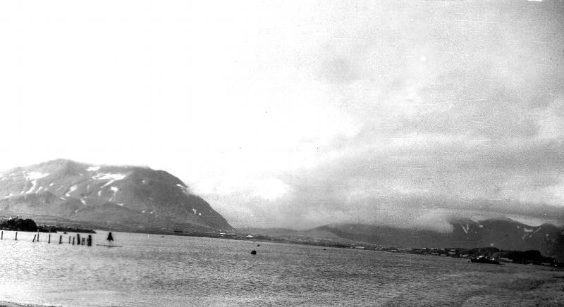 Black and white photo of a bay with mountains in the background