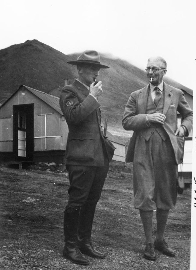 a park ranger and another man standing near a small cabin