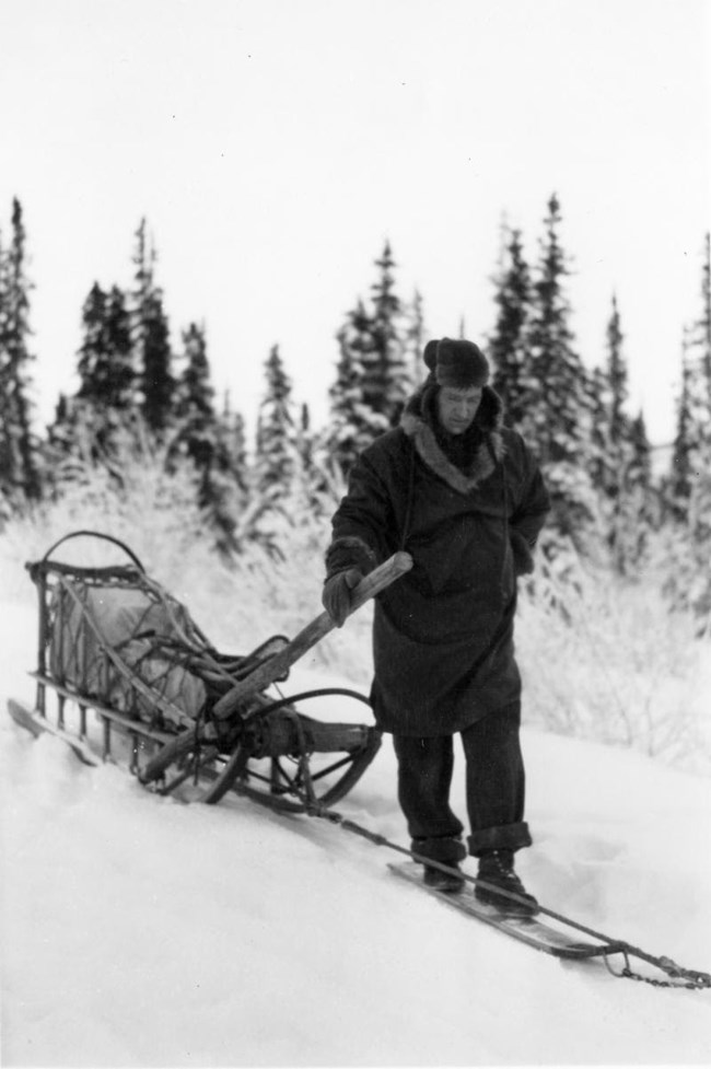 a man pulling a sled in the snow