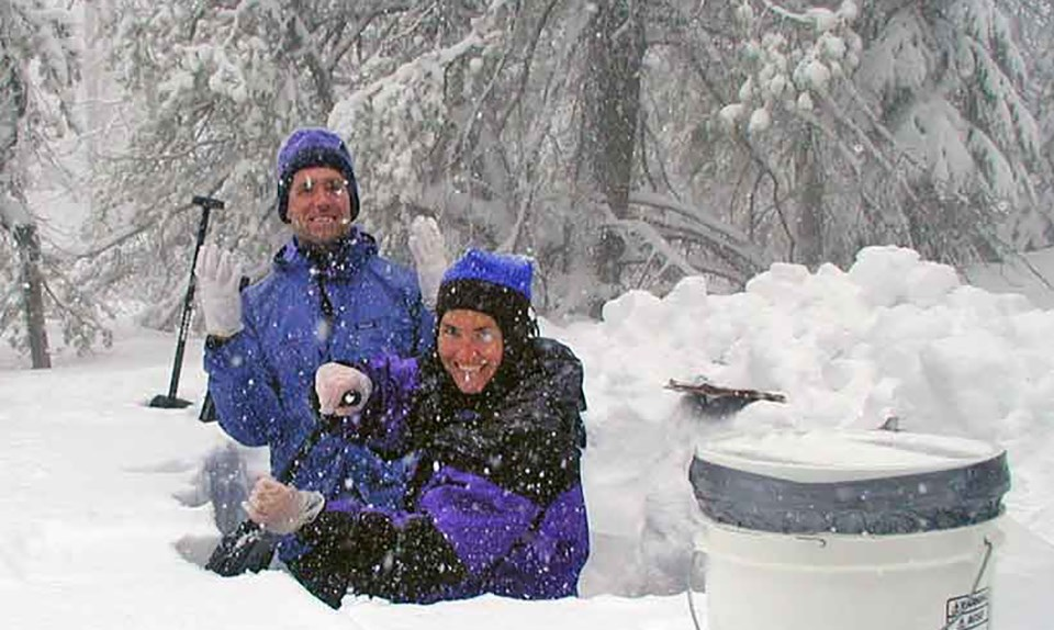 two technicians in colorful winter jackets and hats standing in a snow pit up to their waists, smiling and shoveling snow while snow is falling